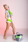 Sexy girl retro style, woman housewife cleaner with mop. Full length sexy girl retro style with mop, woman housewife cleaner in domestic role. Traditional Royalty Free Stock Image
