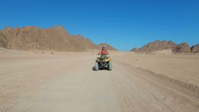 Sexy Girl is Riding a Quad Bike in the Desert of Egypt. Dynamic view in motion. stock video footage