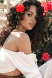 girl with rose in dark curly hair and elegant white outfit, stock photo