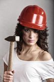 Sexy girl in safety helmet holding hammer tool Royalty Free Stock Photos