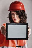 Sexy girl in safety helmet showing tablet Royalty Free Stock Images