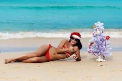 Sexy girl Santa in bikini on a beach fir-tree Stock Photo