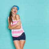 Sexy Girl Shouting And Looking Over Her Shoulder. Beautiful young woman in pink striped shirt, sun visor and jeans shorts looking over shoulder and shouting Royalty Free Stock Photo