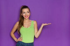 Sexy Girl Showing Product. Smiling beautiful young woman in lime green shirt and jeans shorts holding open hand and looking at copy space. Waist up studio shot Stock Image