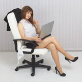 girl sits in an armchair with Royalty Free Stock Image