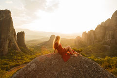 Girl sits on the edge of the cliff and looking at the sun valley and mountains. Girl in red dress sits on the edge of the cliff and looking at the sun valley and stock photos