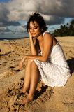 Sexy girl sitting. On the beach in a white dress (high contrast Royalty Free Stock Image