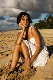 Sexy girl sitting. On the beach in a white dress (high contrast Stock Image
