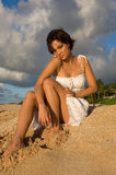 Sexy girl sitting. On the beach in a white dress (high contrast Royalty Free Stock Images
