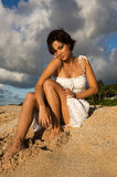 Sexy girl sitting. On the beach in a white dress (high contrast Stock Images