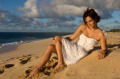 Sexy girl sitting. On the beach in a white dress (high contrast Royalty Free Stock Photography