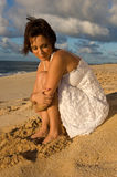 Sexy girl sitting. On the beach in a white dress (high contrast Royalty Free Stock Photo