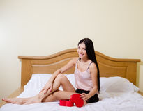 Sexy girl sitting on bed with crossed legs opening Royalty Free Stock Photo