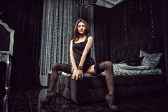 Sexy girl sitting on the bed in sexy dresses and black tights. Royalty Free Stock Photography