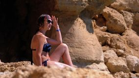 Sexy Girl Sitting on the Cliff on the Rocky Beach of Egypt by the Red Sea. A woman looks into the distance. Rest on the coral and reef beach Sharm El Sheikh stock footage