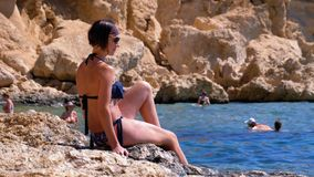 Sexy Girl Sitting on the Cliff on the Rocky Beach of Egypt by the Red Sea. A woman looks into the distance. Rest on the coral and reef beach Sharm El Sheikh stock video