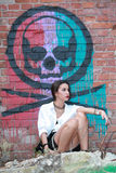 girl sitting down posing with beads on legs in a grunge building with grafittis on the wall Stock Image