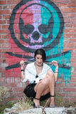girl sitting down posing with beads in mouth in a grunge building with grafittis on the wall Royalty Free Stock Images
