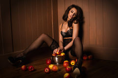 Sexy girl sitting on a floor with apple Royalty Free Stock Photography