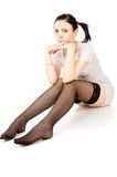 Sexy girl sitting on the floor in white stockings. Barefoot Royalty Free Stock Image