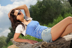 Sexy girl sitting on a log. Glamour girl sitting on a log Royalty Free Stock Photos
