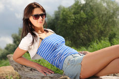 Sexy girl sitting on a log in park Stock Images