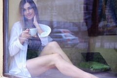 Sexy girl sitting near the window and drinking coffee. single happy woman in white men`s shirt, looking out the window stock image