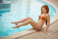 Sexy girl sitting at a pool Royalty Free Stock Image