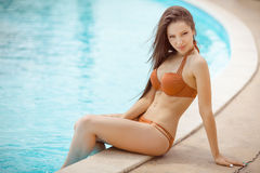 Sexy girl sitting at a pool Stock Photo