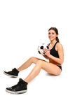 Sexy girl is sitting with a soccer ball on a white background Stock Image