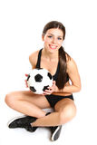 Sexy girl is sitting with a soccer ball on a white background fr Royalty Free Stock Images