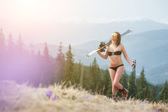 Sexy girl skier is enjoying warm spring, wearing swimsuit, boots and sunglasses. Woman  holding skis on her shoulder Royalty Free Stock Images