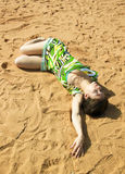 Sexy girl is sleeping on the sand Stock Photos
