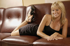 Sexy girl on a sofa. Sexy girl on a brown sofa Royalty Free Stock Photography