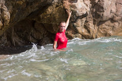 Girl in sportswear and tanga string in a sea cave. Girl in sportswear and tanga string standing in a cave of rocky coast in sea water stock image