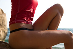 Girl in sportswear and tanga string sitting on the cliff of. The rocky beach royalty free stock photography