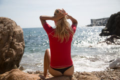 Sexy girl in sportwear and tanga on the rocky beach Royalty Free Stock Photo