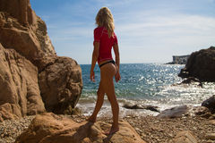 Sexy girl in sportwear and tanga on the rocky beach Stock Photos