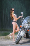 Sexy girl standing by the custom made cruiser motorcycle Royalty Free Stock Image