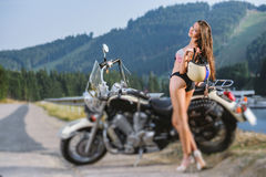 Sexy girl standing by the custom made cruiser motorcycle Royalty Free Stock Photos