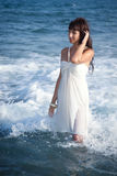Sexy girl standing in the ocean waves Stock Photos