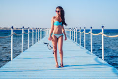 Sexy girl standing on the pear and holding diving equipment Royalty Free Stock Photo