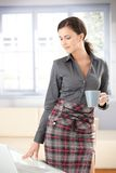 girl standing by table drinking tea Royalty Free Stock Photo