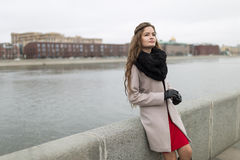 Sexy girl standing on the waterfront in the fall. Girl in a black coat, a scarf and a red dress against a gray sky. Not Isolated. Stock Image