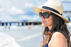 Sexy girl staring in vain at the calm ocean. Sexy brunette girl with beach hat, summer dress and sunglasses staring in vain with the ocean reflection in her Royalty Free Stock Photos