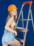 Sexy girl on stepladder over blue Royalty Free Stock Photography