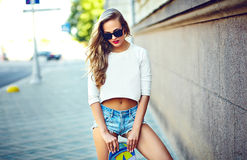 Sexy girl in the street in stylish cloth with skateboard Stock Photography