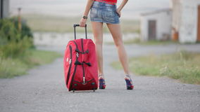 Sexy Girl With Suitcase Walking On The Driveway. Waist down shot of a sexy young girl in mini jeans skirt on high heel with red suitcase walking along the stock footage