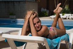 Sexy girl in sun lounger on swimming pool Royalty Free Stock Image
