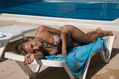 Sexy girl in sun lounger on swimming pool Royalty Free Stock Images